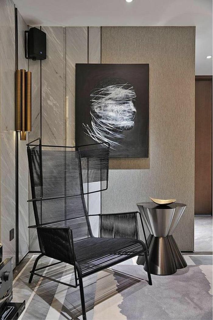 meuble salon pas cher avec des murs en beige et gris, avec des bandes verticales dorées, fauteuil en métal noir, table en métal argenté, surface miroitante, sol revêtu en marbre blanc et rose, tableau avec visage d'homme au mur en noir et blanc