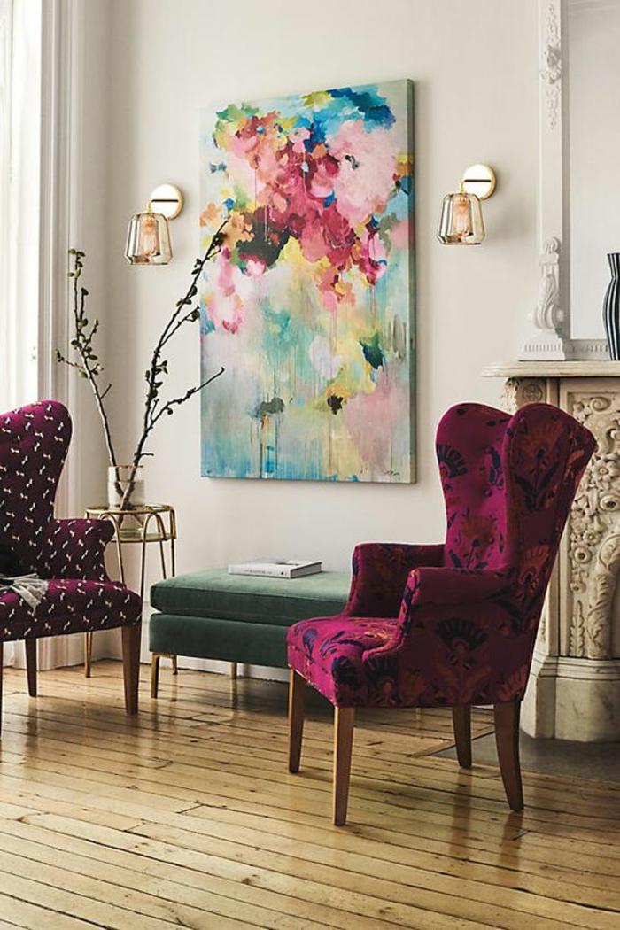 deco salon design avec deux fauteuils en velours fuchsia avec des motifs floraux et des motifs ludiques, grand panneau décoratif au mur en tonalités pastels, deux appliques murales en métal doré, parquet en bois rude laqué, cheminée avec des ornements baroques