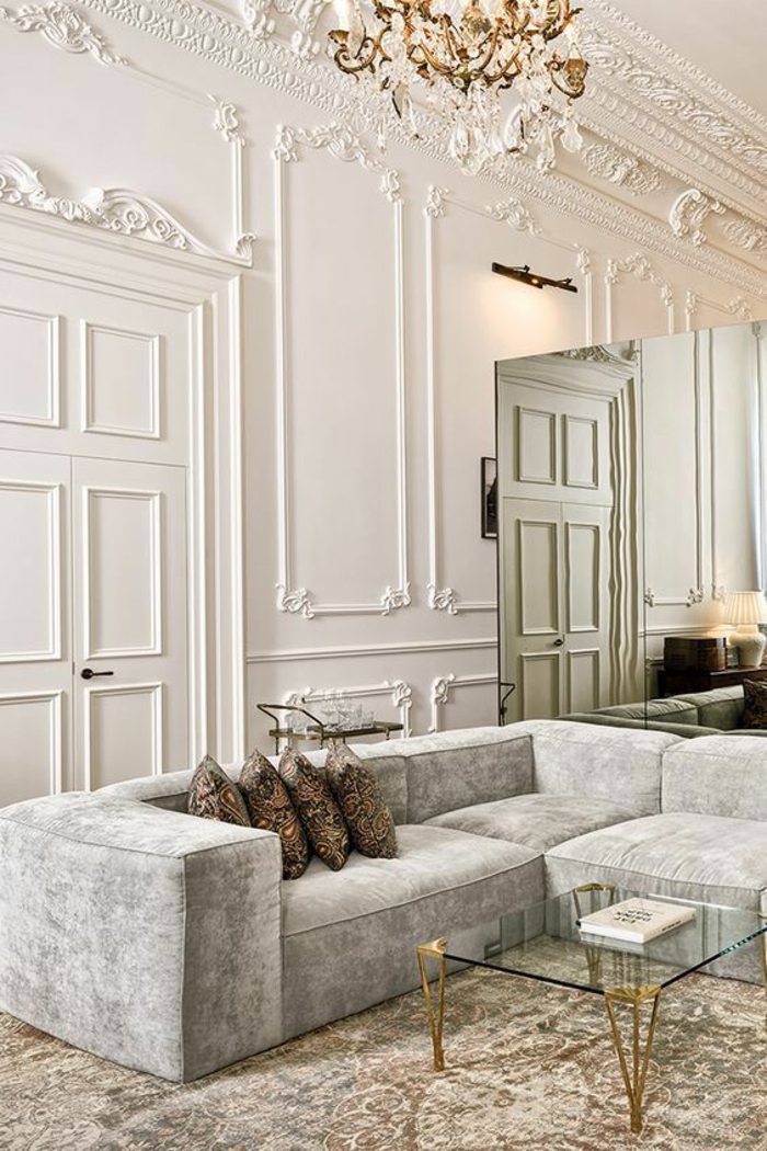 deco salon, idée deco salon, portes et murs blancs avec des frises rococo et baroques, lustre en pampilles de cristal, avec des éléments dorés, canapé angulaire en gris perle, tapis en nuances dorées et blanches, grand miroir posé comme séparateur d'espace, table carrée en métal doré avec plan en verre blanc