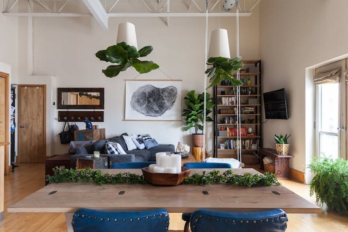 etagere industrielle en bois et metal, meuble style industriel dans un salon avec canapé gris, plantes suspendues, table en bois et chaises bleues, armature apparente