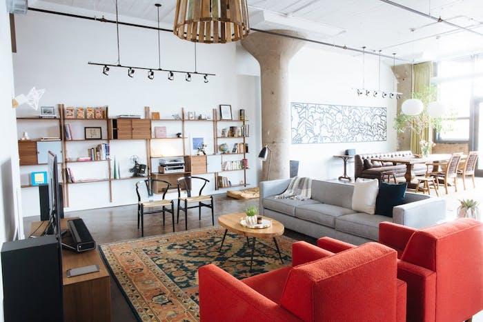 décoration industrielle salon avec canapé gris, fauteuils rouges tapis oriental, table basse minimaliste bois et metal, parquet foncé etagere en bois, luminaire de spots