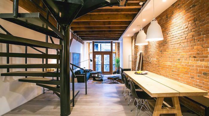 exemple de salon style industriel avec canapé noir, tapis oriental, table basse, petite salle à manger adjacente, mur en briques, suspensions industrielles escalier helicoidal, poutres apaprentes