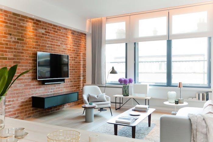 exemple de deco style industriel dans un salon simple avec canapé et fauteuil blanc, table basse en bois, mur en briques, meuble tv noir