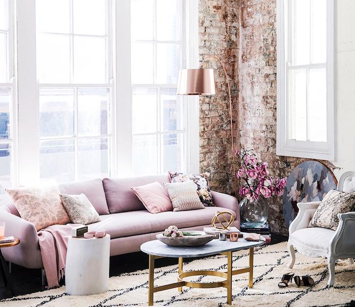 exemple de deco style industriel dans un salon feminin avec canapé rose, table basse marbre et laiton, tapis noir et blanc, mur en briques, luminaire rose gold