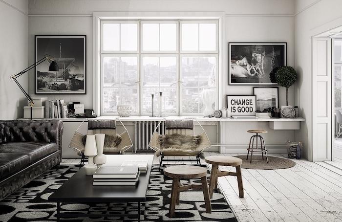 décoration industrielle salon scandinave avec canapé noir, table basse noire, tapis gris et noir, tabourets en bois, chaise avec peau animal, deco graphique de tableaux en noir et blanc, parquet blanchi