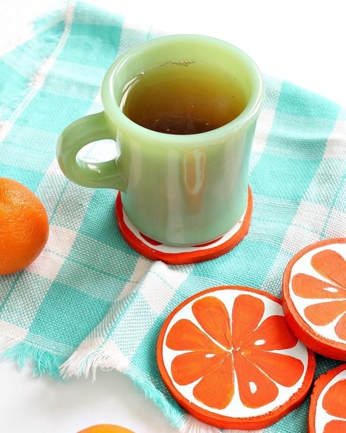 des dessous de verre en rondins de bois customisés de peinture orange et blanche, exemple cadeau fête des pères à fabriquer