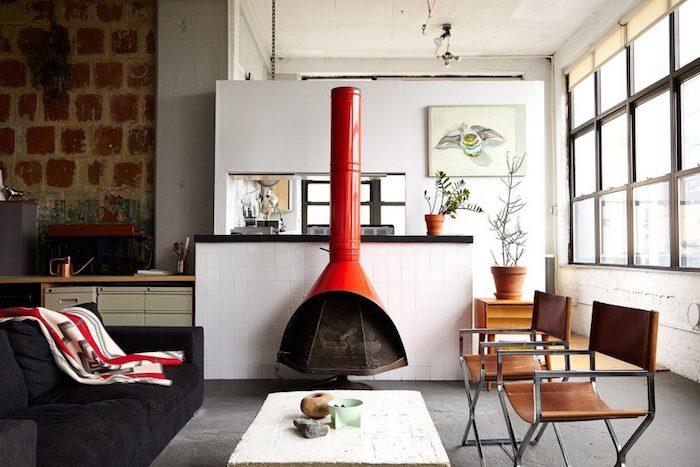 meuble style industriel, chaises en cuir et métal, revêtement sol gris, canapé noir et cheminée rouge