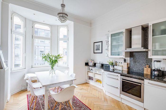 modele de cuisine blanche avec avec plan de travail gris foncé, parquet clair, tapis oriental, table et chaises blanches svandinaves