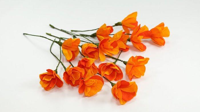 comment faire des fleurs en papier, exemple de fleurs couleur orange à grosses pétales et tiges vertes de fil de fer