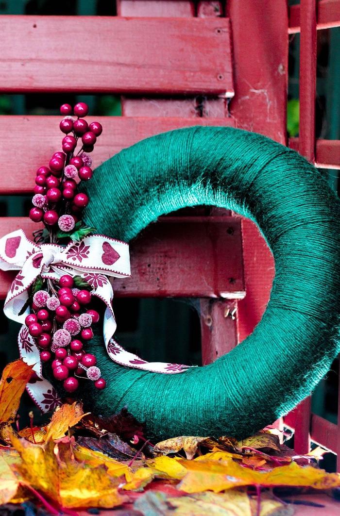 idées créatives pour une couronne de noel a faire soi meme, jolie couronne de noël revêtue de fil vert et décorée de fruits rouges artificiels