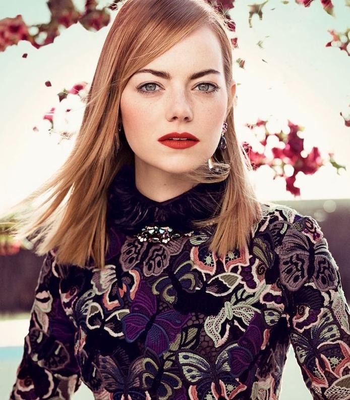 emme stone et sa coloration rousse sur un carré mi long lisse avec une meche asymetrique, des yeux bleus et robe noire à motifs papillon