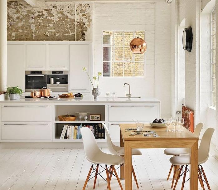 cuisine blanche laquée avec comptoir blanc, parquet blanchi, coin repos table bois et chaises scandinaves, mur usé, suspension cuivre