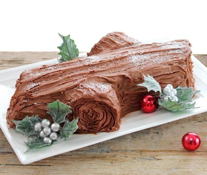 exemple de gâteau, biche de noel classique avec nappage gateau au chocolat et décoration de feuilles de houx, perles argentées et boules de noel rouges autour