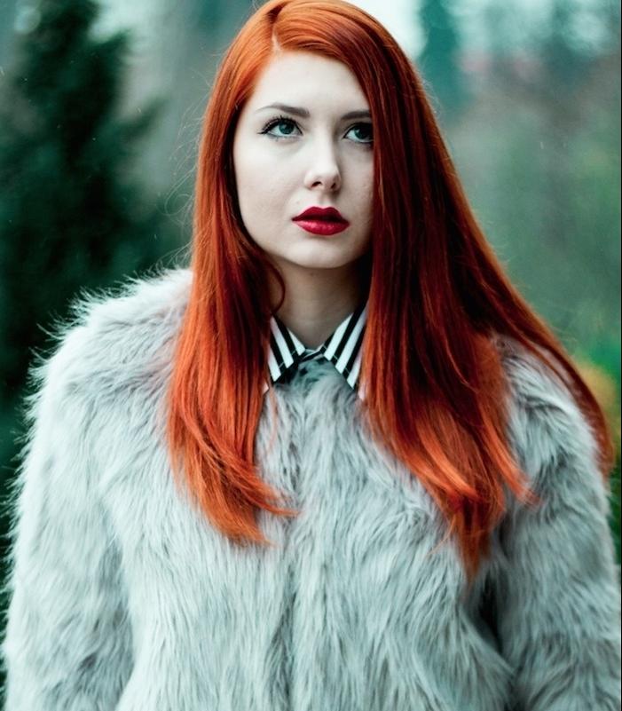 modele de cheveux cuivré avec des éclats roux et rouges, coiffure simple, cheveux lisses, blouson en peau animale