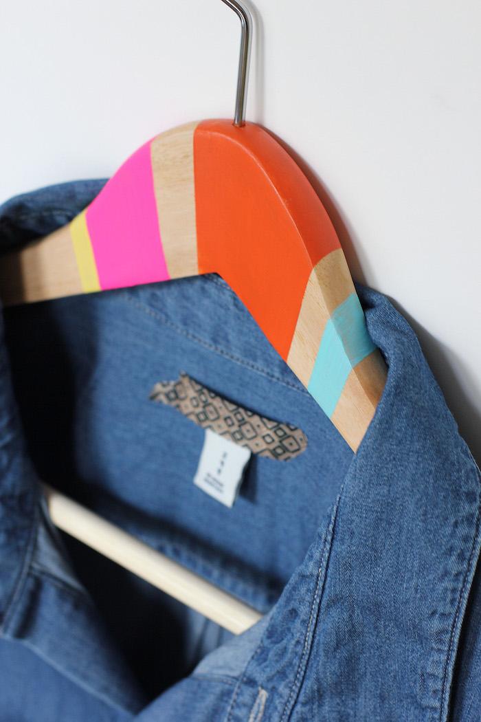 diy cadeau original, un cintre en bois décoré de bandes de peinture rose, orange, jaune et bleue