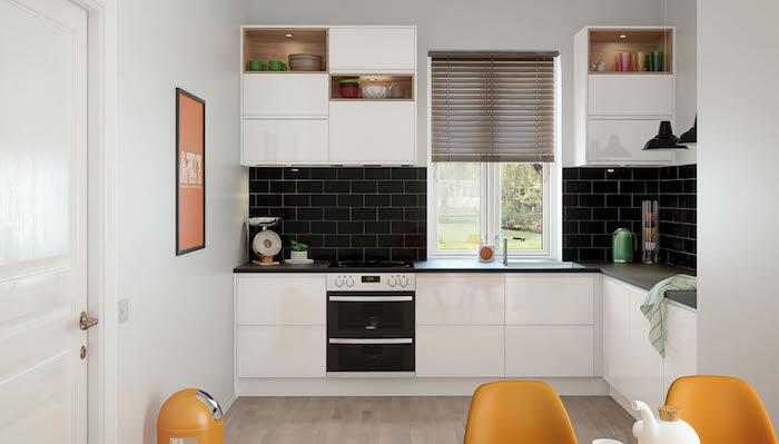 cuisine blanc laqué avec credecne carrelage noir, parquet bois, chaises orange, plan de travail noir, étagères ouvertes éclairées