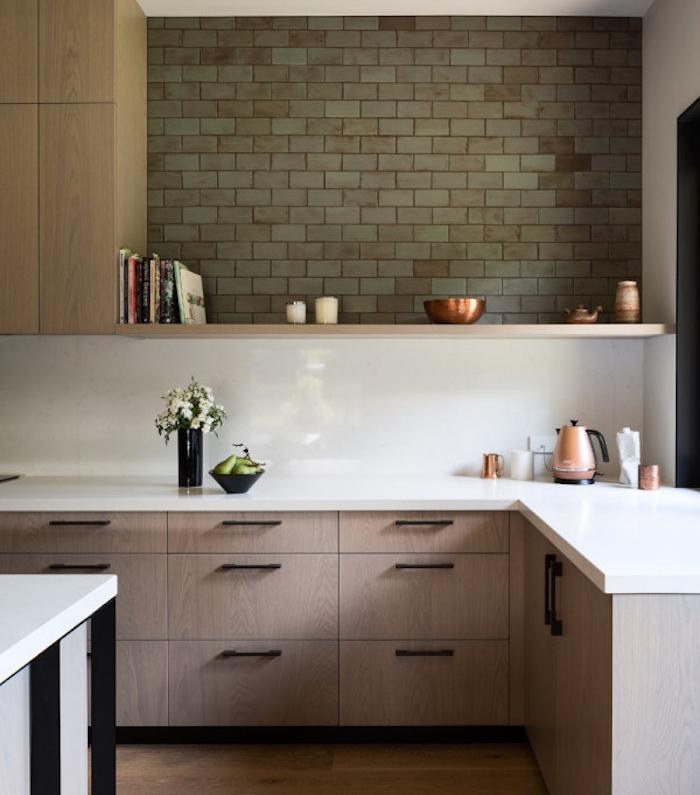 modele de cuisine equipee avec meuble bas en bois et plan de travail blanc, etagere en bois et pan de mur en briques vertes, accessoires deco interessants