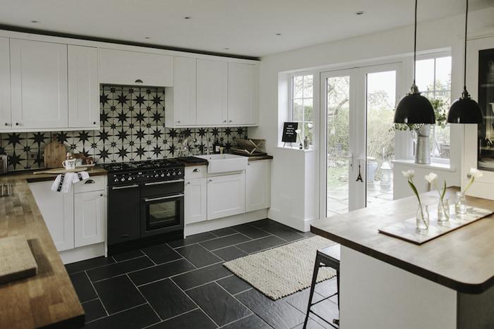 modele de cuisine blanche et noire avec sol carrelage noir, meubles bas et hauts blancs, carrelage blanc à étoiles, plan de travail bois, ilot central avec suspensions noires