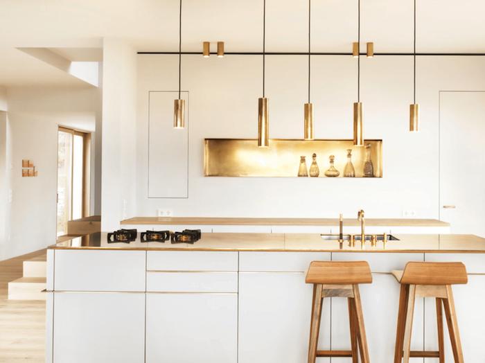 cuisines équipées, modele de cuisine bois et blanc, avec rangement encastré dans un mur couleur dorée et suspensions or, tabourets en bois
