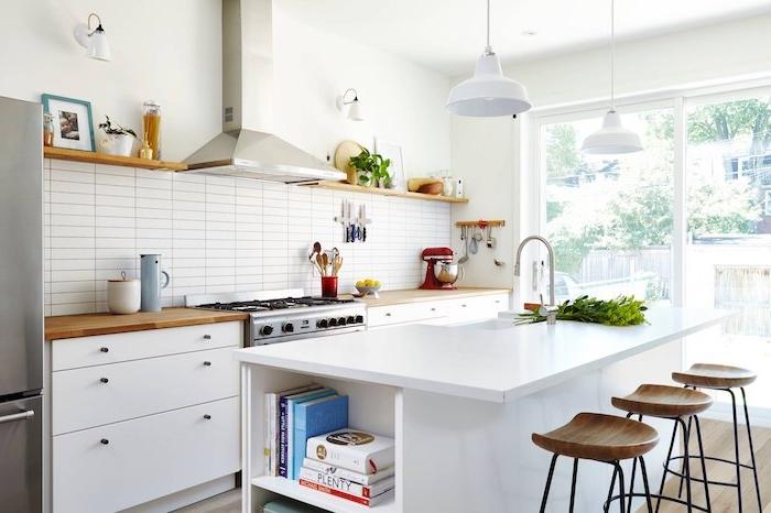 cuisine améangée avec facade et comptoir blanc, parquet bois clair, aspirateur inox, credence en carrelage blanc, suspensions blanches, etagere bois ouverte