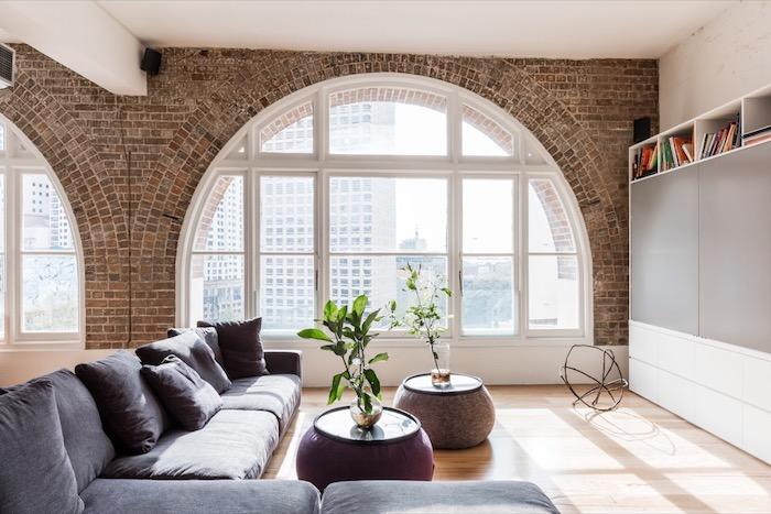 décoration industrielle salon avec canapé d angle gris, table basse pouf mauve et gris, parquet clair, mur en briques et baie vitrée