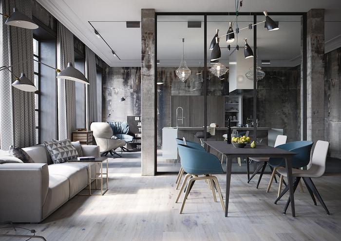 cuisine ouverte sur salon industriel, avec canapé et petite table basse en laiton avec plateau noir, salle à manger en chaises scandinaves et table bois grise, luminaires industriels