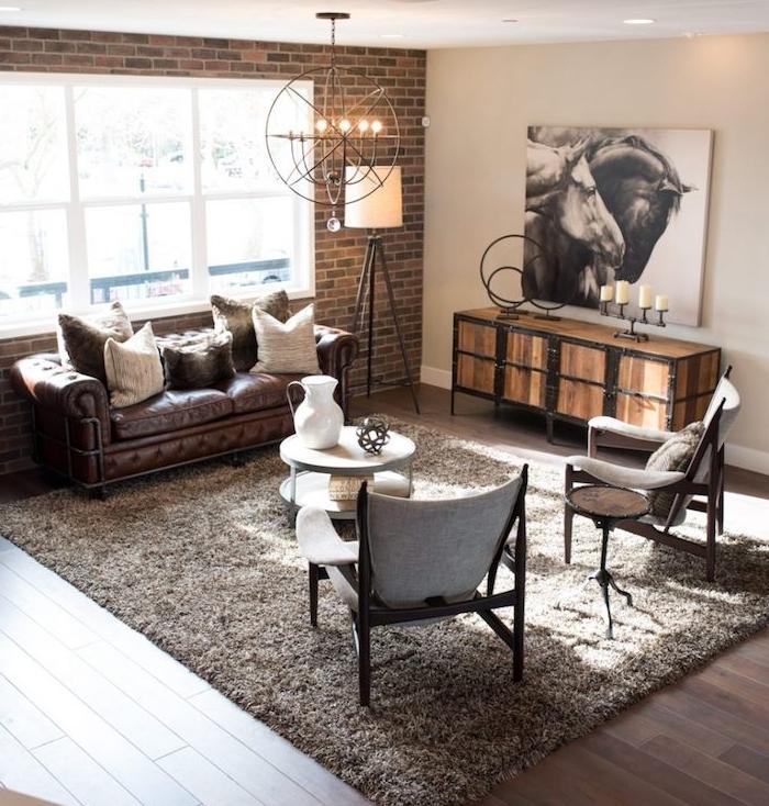 meuble style industriel dans un salon, canapé en cuir marron foncé, table basse à roulettes blanche, chaises vintage, meuble en bois et métal, suspension industrielle, mur en briques