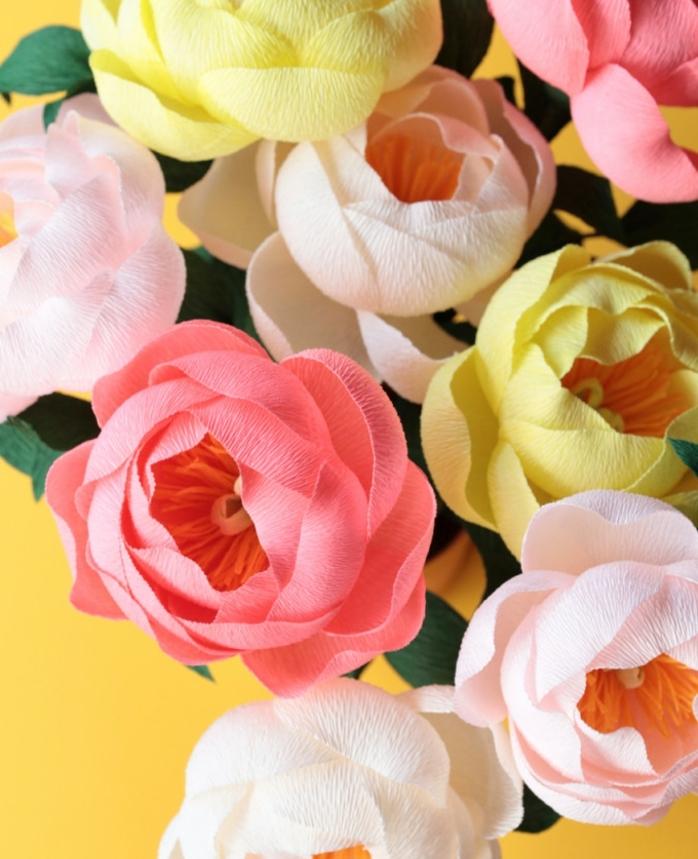 fleurs en papier crépon, pivoines couleur rose et jaune avec des feuillages vertes, petales rose, jaunes et blanches