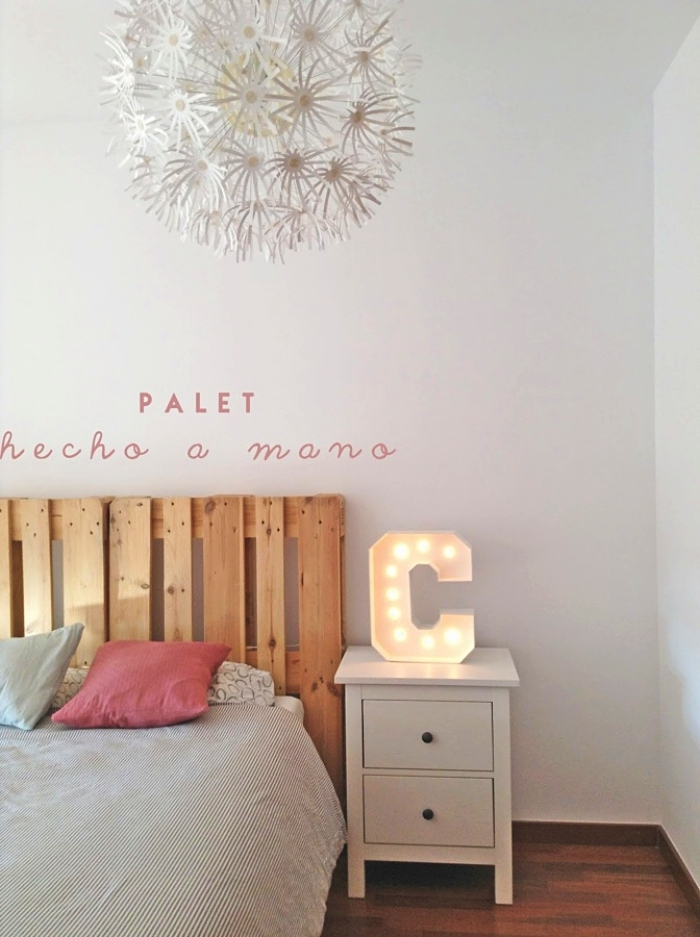 tete de lit en palette, chambre à coucher blanche avec parquet en bois et grand lit décoré de coussins rose et bleu