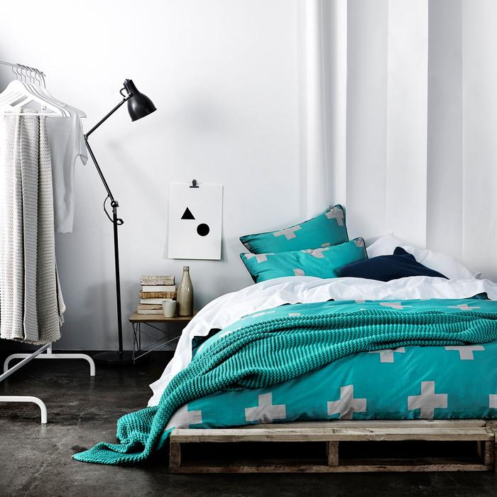 une chambre à coucher monochrome et minimaliste avec un lit palette bas