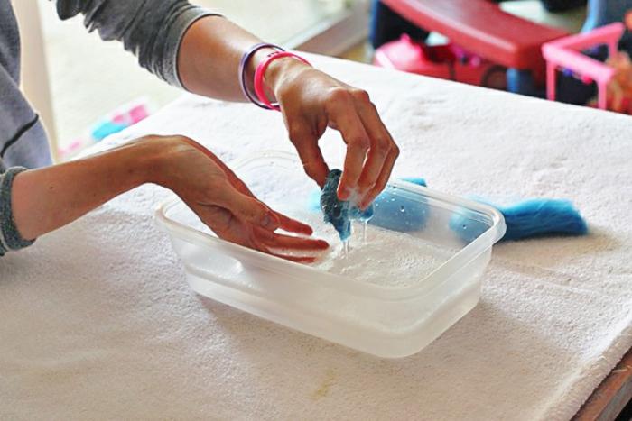 former des boules avec de la laine mouillée, boules bleues trempées en l'eau