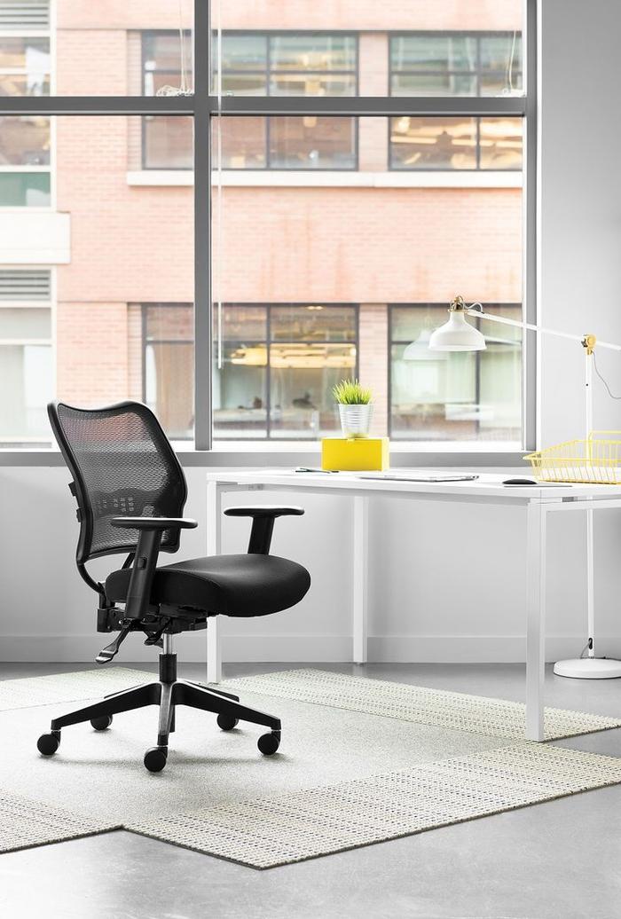 espace bureau minimaliste et élégant équipé avec un fauteuil de bureau à design ergonomique en tissu maille qui permet au corps de respirer