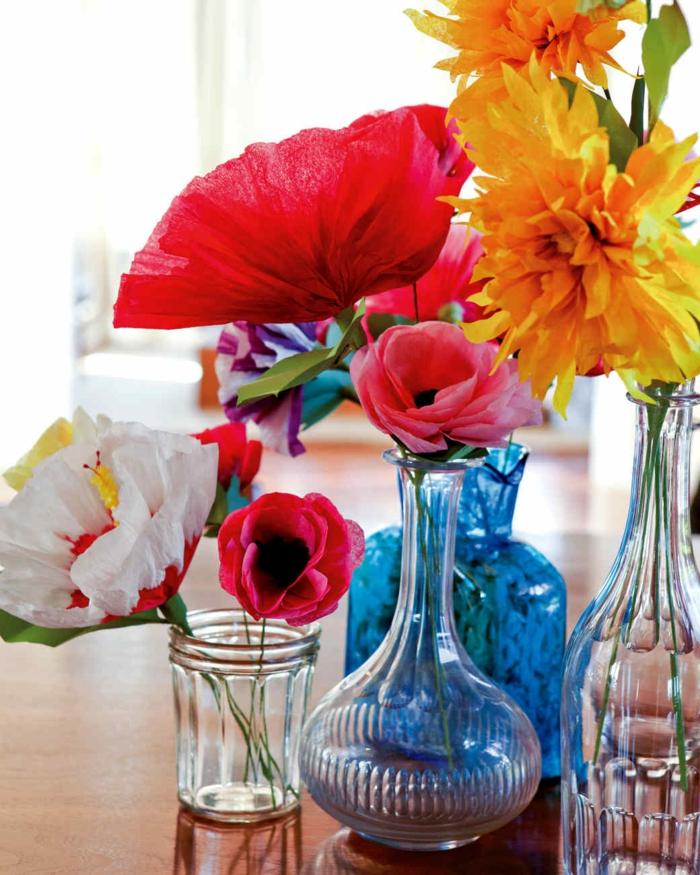 des dleurs en papier crépon et en papier de soie dans un vase, pot et bouteille en verre, fleurs couleur rose, rouge et jaune simples