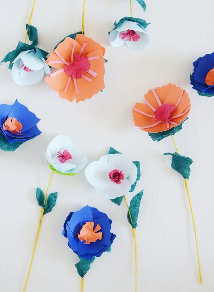 exemple de fleur en papier facile, pétales de papier blanc, bleu et orange, tiges en fil de fer jaune et feuilles vertes