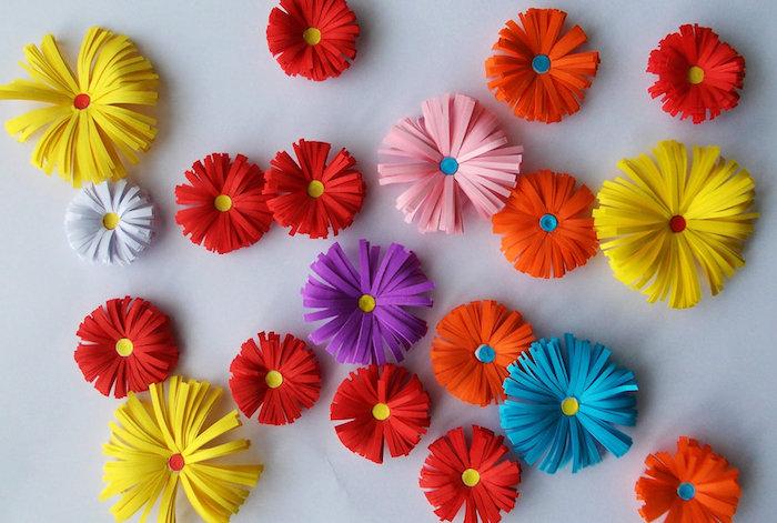 comment faire des fleur en papier, décoration murale de papier à franges couleur violette, rose, rouge et jaune sur un mur