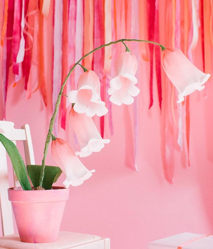 fleur en papier crepon rose, type jacinthe dans un pot de terre cuite repeint en rose et chutes de tissu sur le fond