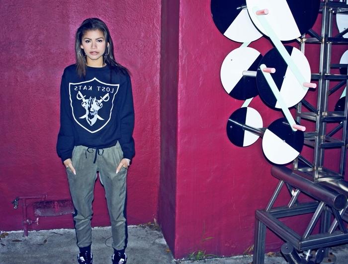 fond d'écran stylé swag, photo de jeune femme swag au pantalon kaki et sweatshirt noir avec baskets noirs