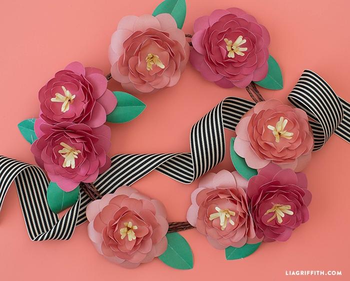 comment faire des fleurs en papier rouge avec un centre jaune de papier frangé et feuilles vertes artificielles, diy guirlande decorative