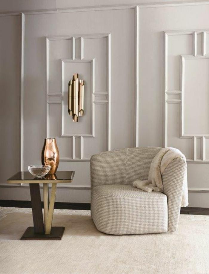 salon de luxe avec fauteuil semi-rond en couleur blanc crème, murs en blanc, avec des frises en forme de rectangles blancs, table carrée en blanc et noir, tapis en beige, vase décoratif en bronze