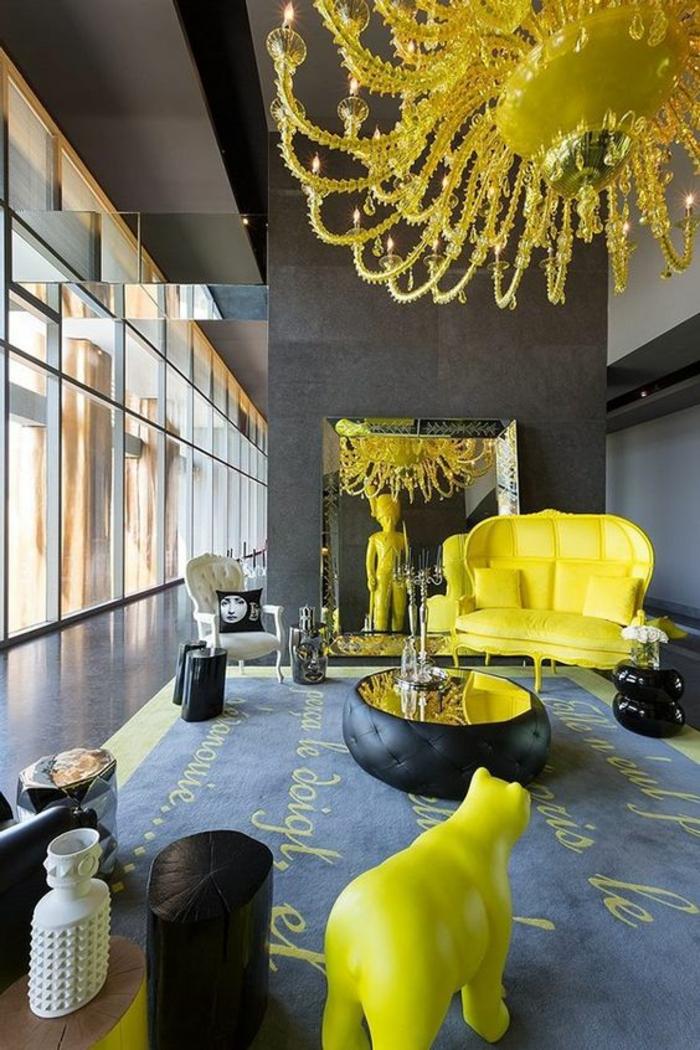 deco salon idée deco salon avec luminaire, canapé et figure d'ours décoratif en couleur jaune flashy, tapis gris anthracite avec des inscriptions en jaune, table ronde et colonne en taupe