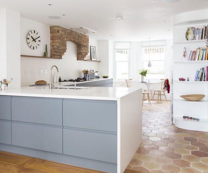 amenagement cuisine en l avec meubles cuisine gris et plan de travail blanc, petite bibliotheque blanche, sol carrelage terre cuite, accent en briques