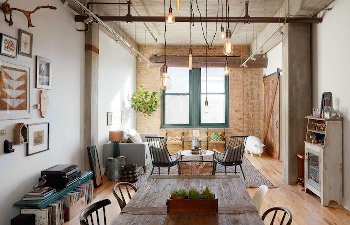 salon industriel design avec tuyauterie apparente et suspensions en ampoules dénuées, chaises metalliques, mur en briques, parquet clair, ouverture sur salle à manger