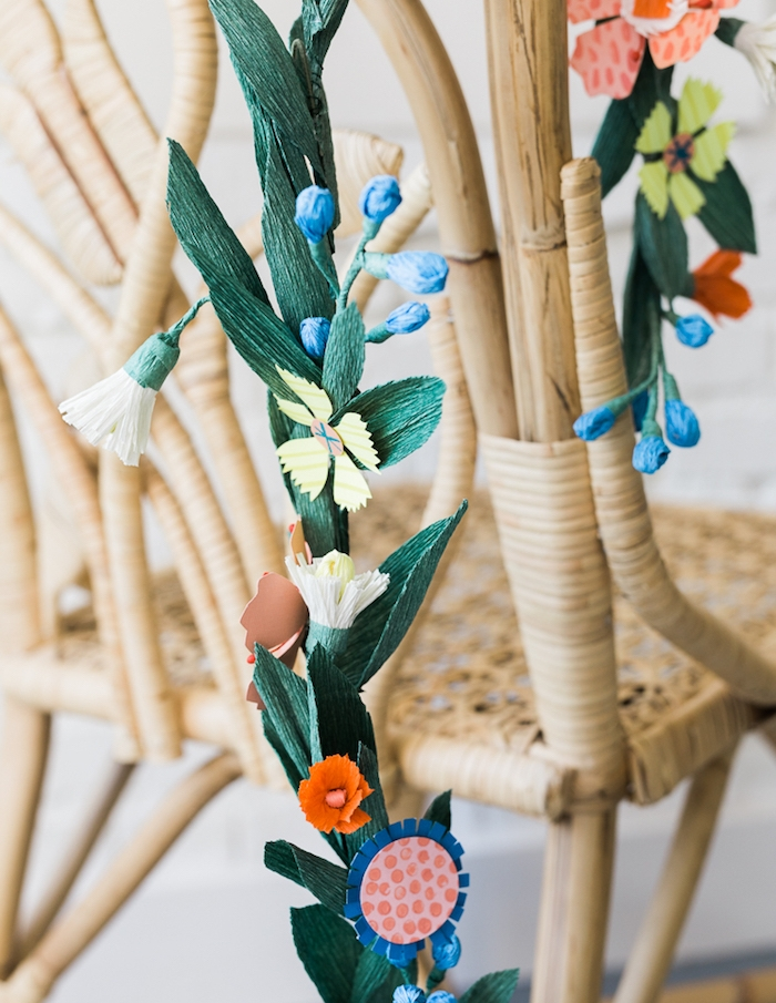une guirlande en papier diy avec fleurs papier crepon et feuilles vertes en crépon sur le dossier d une chaise en rotin