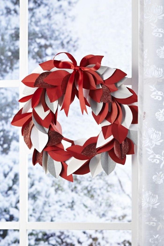 décoration de noel à fabriquer pour adultes, une couronne de noël en blanc et rouge réalisée avec des feuilles en papier, fixée à la fenêtre à l'aide d'un joli noeud satiné