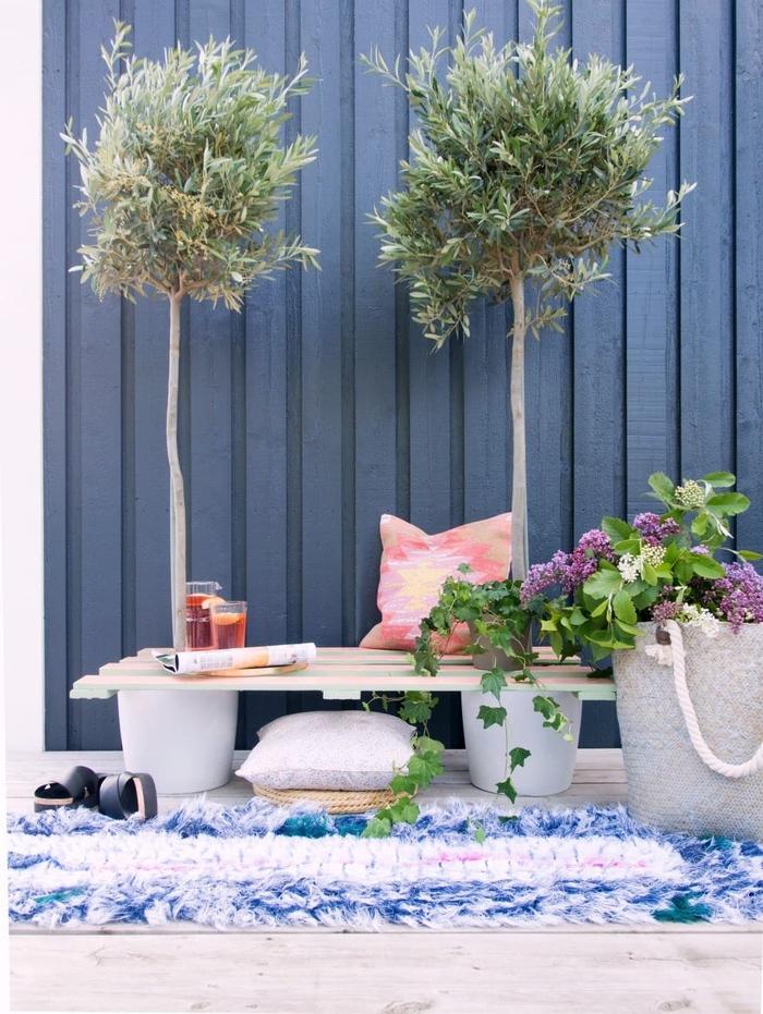 idée créative pour relooker la terrasse en créant un coin de repos avec banc palette posé entre deux arbres en pots