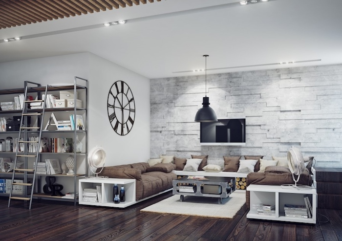 meubles industriels dans un salon avec table basse à roulettes, canapé blanc avec rangements et coussins d assise marron, suspension noire, horloge vintage, mur en pierre