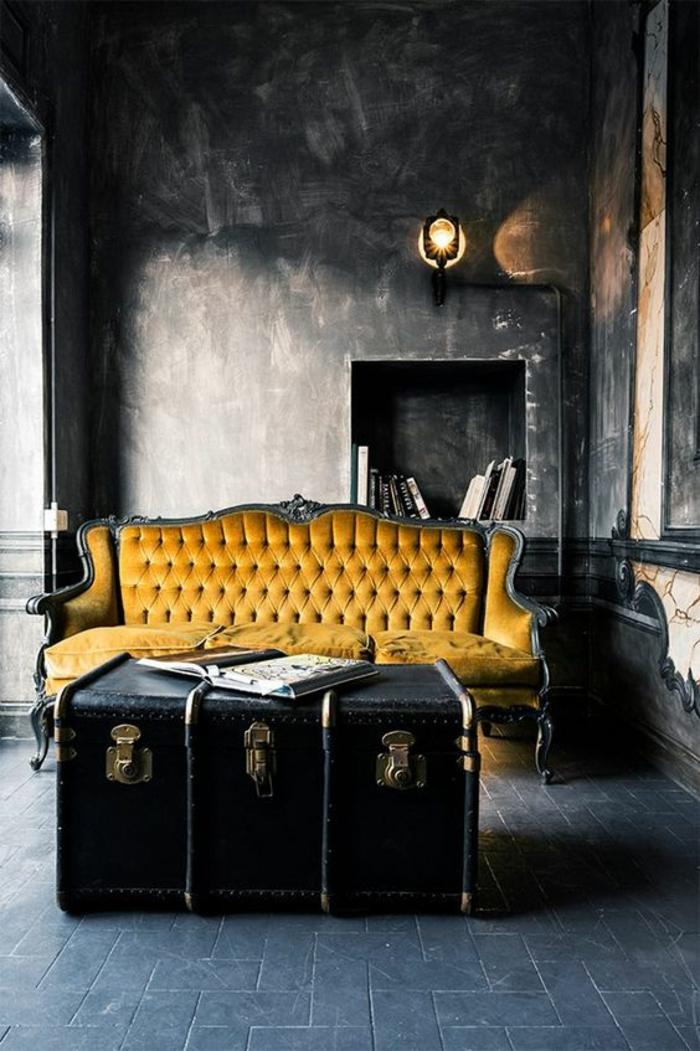 deco sejour, maison moderne de luxe, avec canapé en jaune moutarde, et bois noir, murs en gris anthracite, carrelage en dalles gris anthracite, grande malle en noir avec des fermoirs en métal jaune