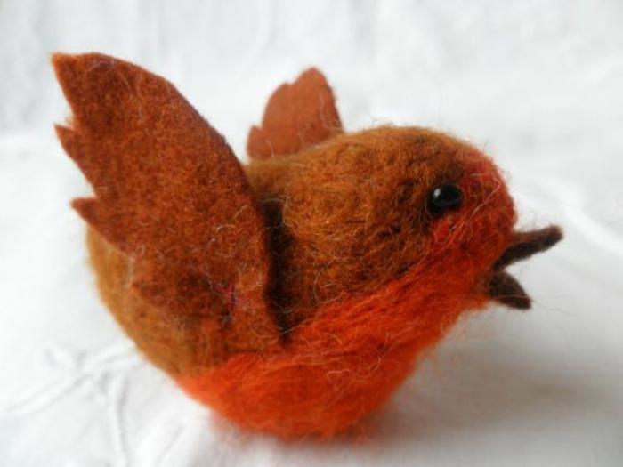 joli oiseau orange fabriqué à partir de la laine cardée, créer des figures avec de la laine
