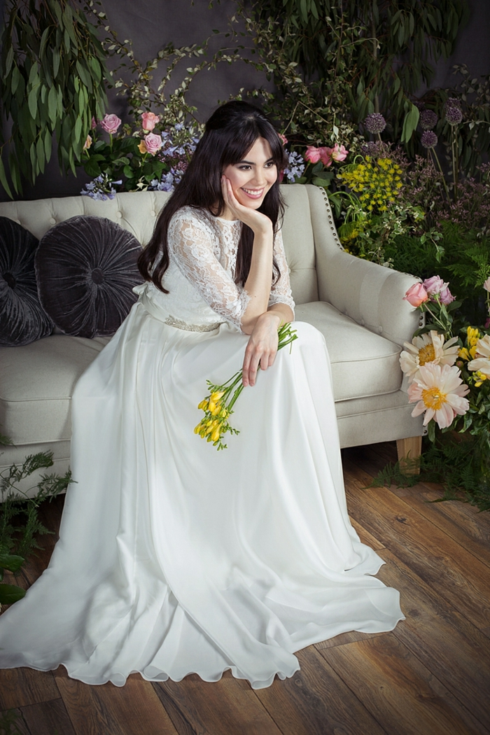 robe de mariée blanche, manches en dentelle, sofa gris clair, bouquet de fleurs jaunes