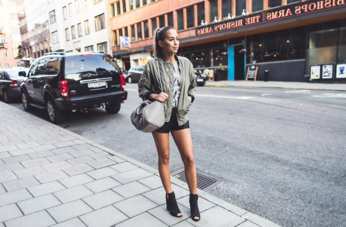 bomber femme, tenue en shorts de cuir noir et blouse grise combinés avec bottines noires ouvertes devant